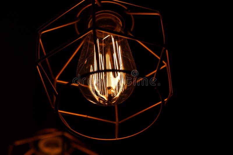 在黑暗的背景的葡萄酒下垂电灯泡爱迪生 创造性Сoncept  老葡萄酒电灯泡 库存照片