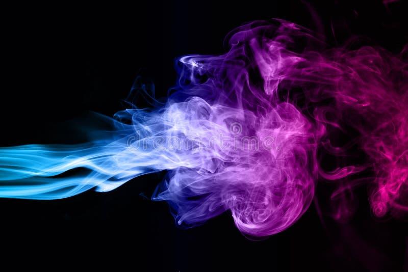 在黑暗的背景的蓝色和桃红色烟 库存照片