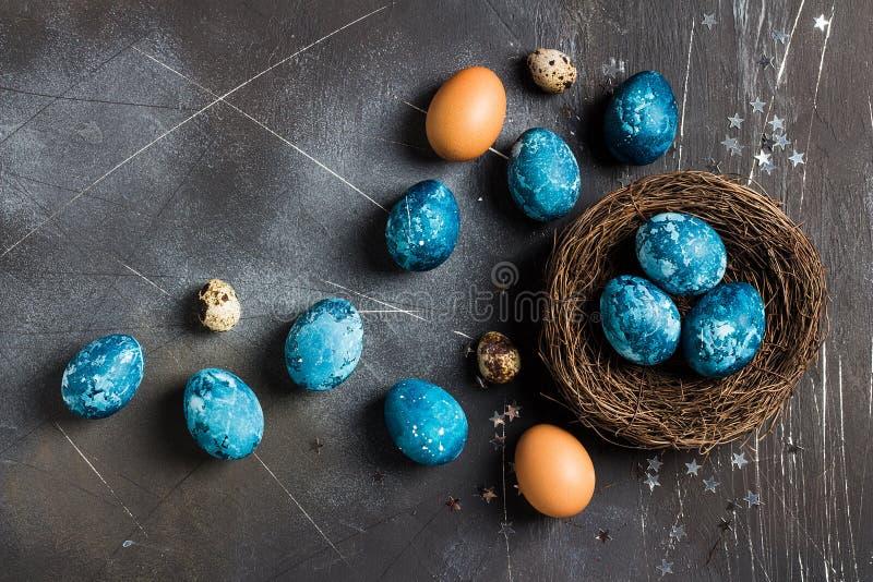 在黑暗的背景的蓝色颜色用手绘的巢的复活节彩蛋 免版税图库摄影