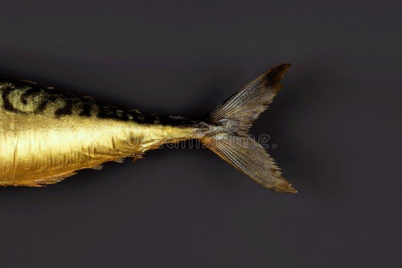 在黑暗的背景顶视图的熏制的鲭鱼 免版税库存照片