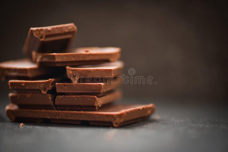 在黑暗的背景/关闭堆积的巧克力块巧克力片和大块糖果甜点心和快餐 图库摄影