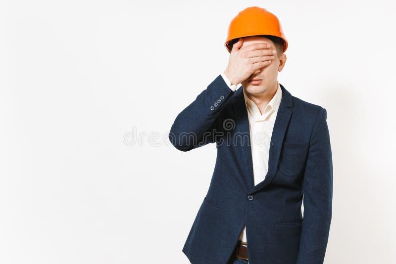 在黑暗的衣服的年轻英俊的紧张商人,防护建筑橙色盔甲用被隔绝的棕榈盖面孔 库存照片