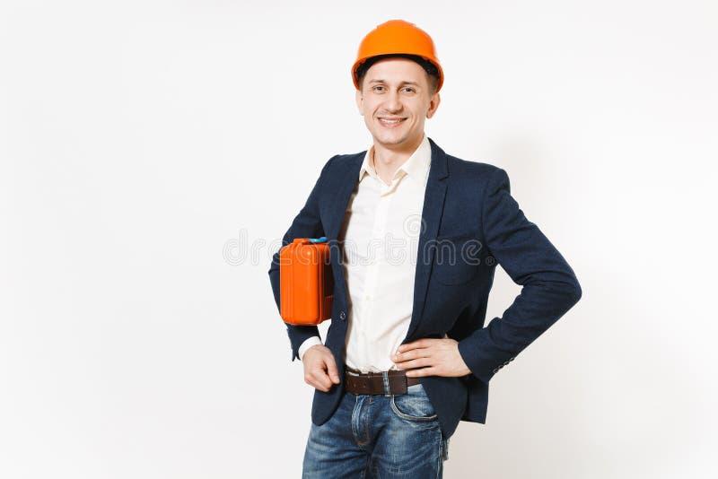 在黑暗的衣服的微笑的商人,与仪器的防护安全帽藏品事例或工具箱和保持胳膊在腰部 库存照片