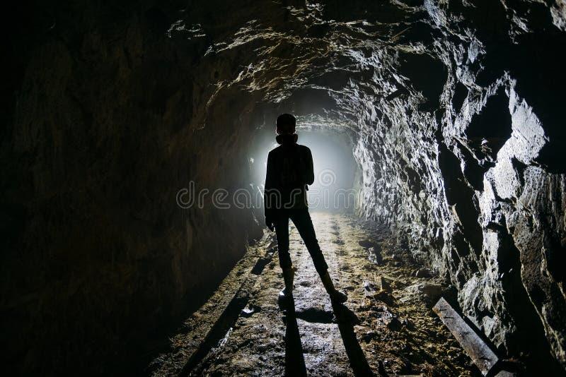 在黑暗的被放弃的矿里面的蠕动的由后面照的人的剪影 图库摄影