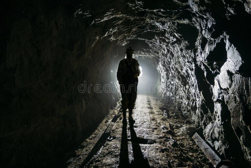 在黑暗的被放弃的矿里面的蠕动的由后面照的人的剪影 免版税图库摄影