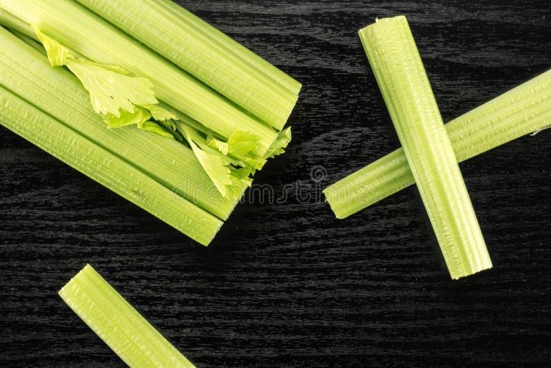 在黑木头的新鲜的绿色芹菜 免版税库存照片