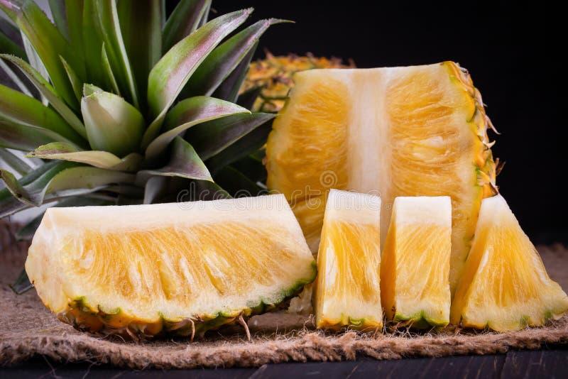 在黑木头,黑背景的新鲜的菠萝 库存图片