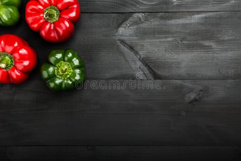 在黑木背景的红色和青椒 农业新鲜市场产品蔬菜 图库摄影