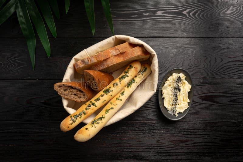 在黑木背景的面包篮子 免版税库存照片