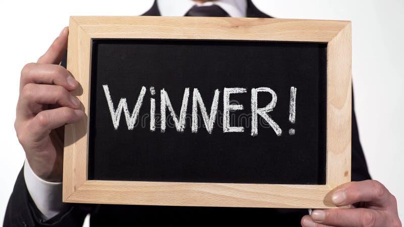 在黑板写的优胜者惊叫在商人手,成功的人 库存照片