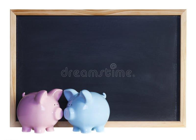 在黑板前面的存钱罐夫妇 库存图片