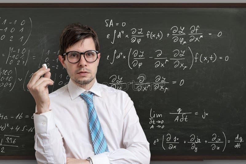 在黑板前面的年轻老师有算术等式的 免版税图库摄影