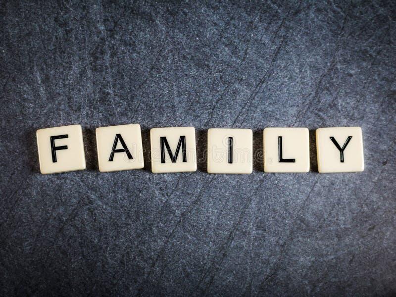 在黑板岩背景拼写家庭的瓦片上写字 库存图片