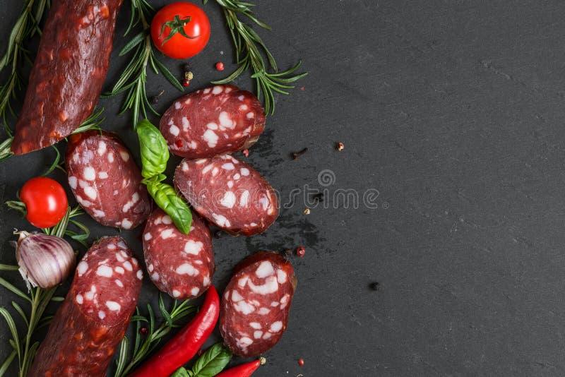 在黑板岩背景的熏制的切的蒜味咸腊肠 香肠用迷迭香、蓬蒿、蕃茄和胡椒 顶视图 库存照片