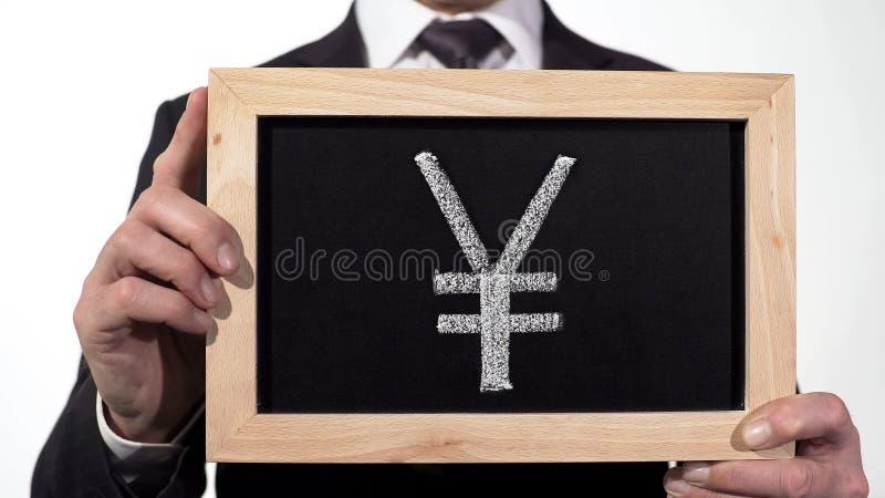 在黑板画的元标志在商人手上,中国货币,亚洲 免版税库存照片