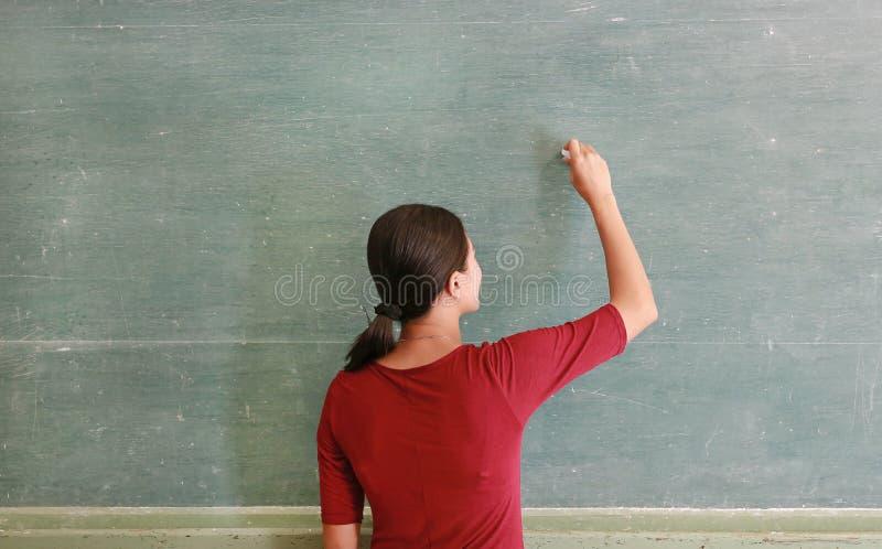 在黑板的亚洲老师文字有白垩的在教室 库存图片