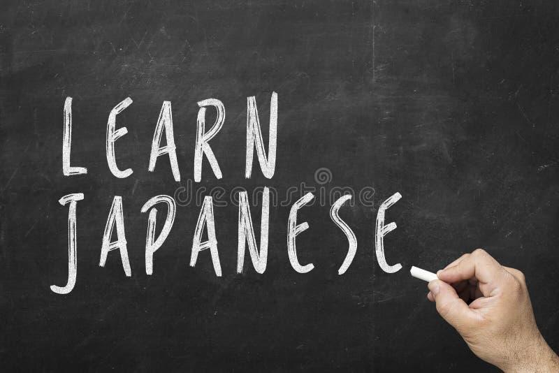 在黑板的人的手文字文本:学会日语 库存图片