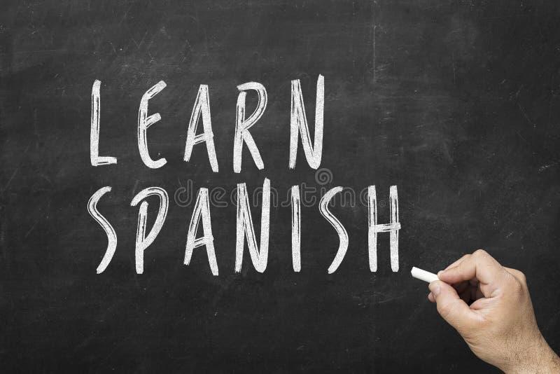 在黑板的人的手文字文本:学会西班牙语 图库摄影
