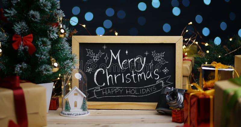 在黑板的圣诞快乐印刷术在圣诞节装饰之间 库存照片