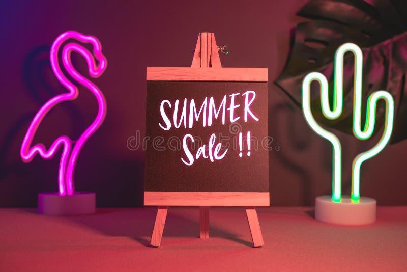 在黑板的夏天销售有火鸟和仙人掌霓虹桃红色和蓝色光的在桌上 增加的文本假装模板 图库摄影
