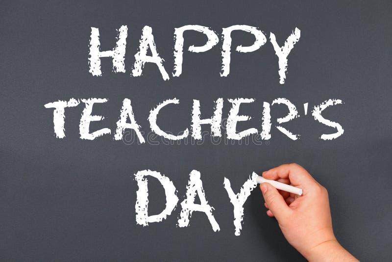 在黑板的文本白垩:愉快的老师的天 学校用品,办公室,书,苹果 免版税图库摄影