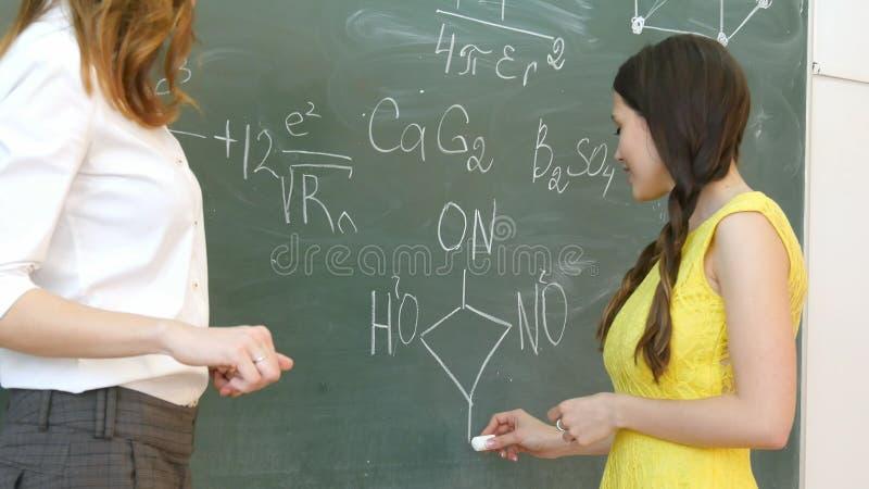 在黑板的相当微笑的年轻女性大学生文字在化学班期间 免版税库存照片