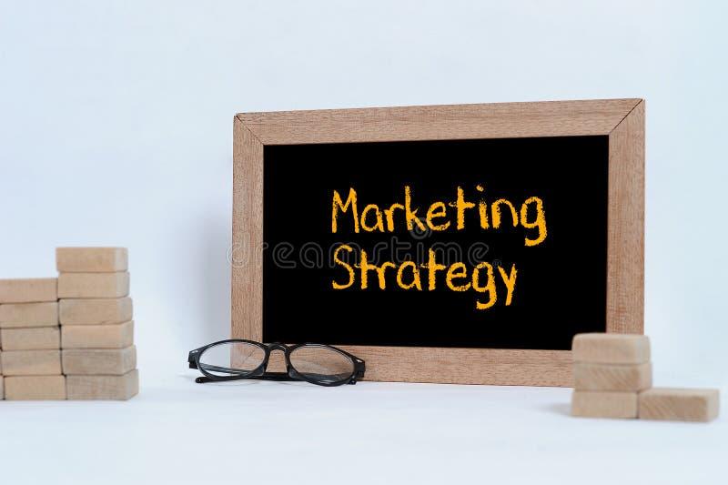 在黑板的营销策略题字 堆积当步台阶的眼睛玻璃和木刻 库存照片
