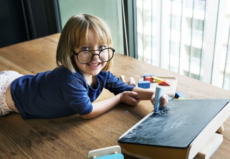 在黑板的逗人喜爱的小女孩图画 免版税图库摄影