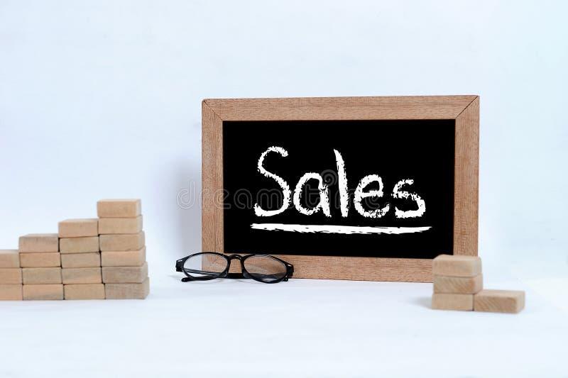 在黑板的销售题字 堆积当步台阶的眼睛玻璃和木刻 库存图片