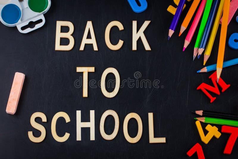 在黑板背景的学校用品与拷贝空间 图库摄影