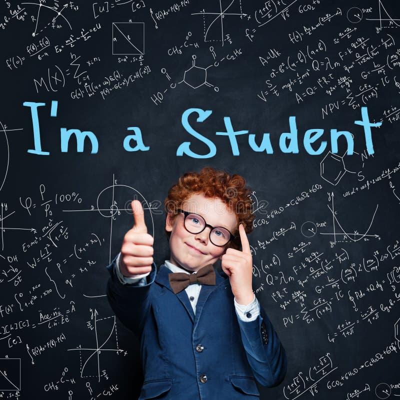在黑板背景的聪明的儿童男小学生陈列赞许 r 免版税库存图片