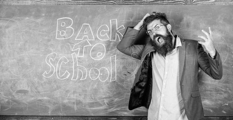 在黑板附近的老师或教育家立场有回到学校的题字的 老师不快乐呼喊歇斯底里面对 免版税库存照片