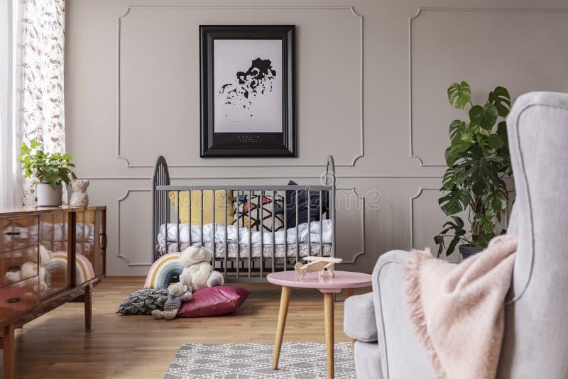 在黑框架的地图在灰色小儿床上 库存图片