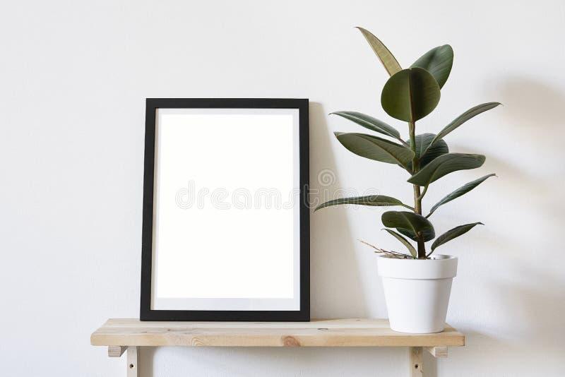 在黑框架的海报在墙壁上的白色时髦的现代内部在绿色沙发上 设计模板大模型 免版税库存图片
