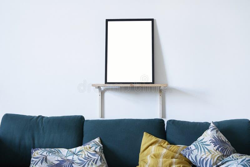 在黑框架的海报在白色墙壁,绿色沙发上的北欧时髦的现代内部在客厅 设计版面的空的空间 免版税库存照片