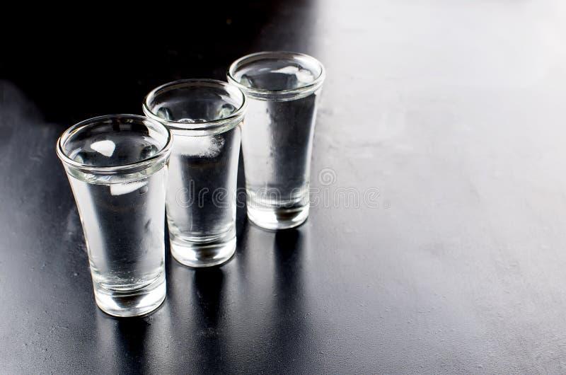 在黑桌上的伏特加酒射击 免版税库存图片
