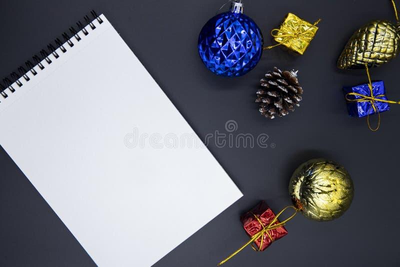 在黑桌上的白皮书笔记薄与圣诞树装饰 商标、字法或者剪影的寒假大模型 库存图片