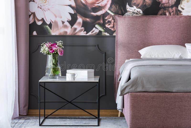 在黑桌上的花在卧室inte的桃红色和灰色床旁边 免版税库存图片