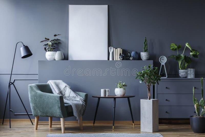 在黑桌和植物旁边的绿色扶手椅子客厅inte的 免版税库存图片
