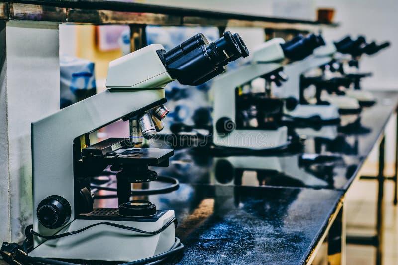 在黑桌顶部的白色显微镜 免版税图库摄影