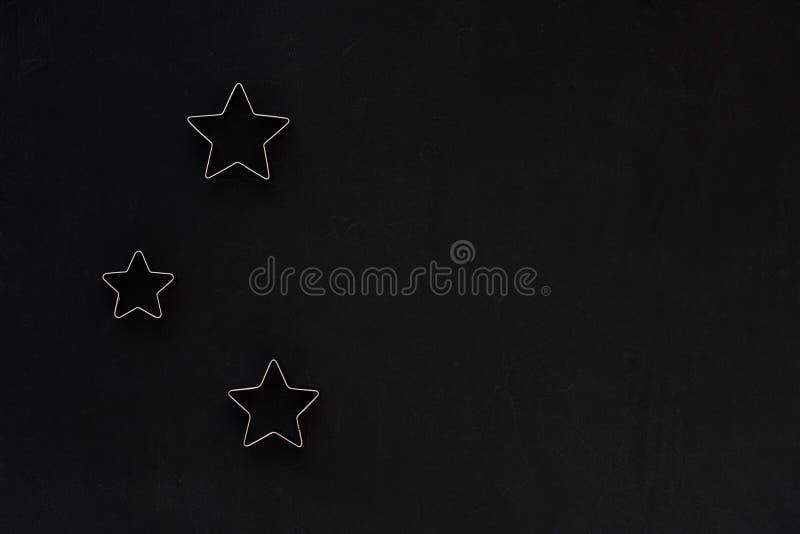 在黑欢乐背景的金属星 烘烤的模子 曲奇饼切削刀 平的位置,顶视图 免版税库存照片