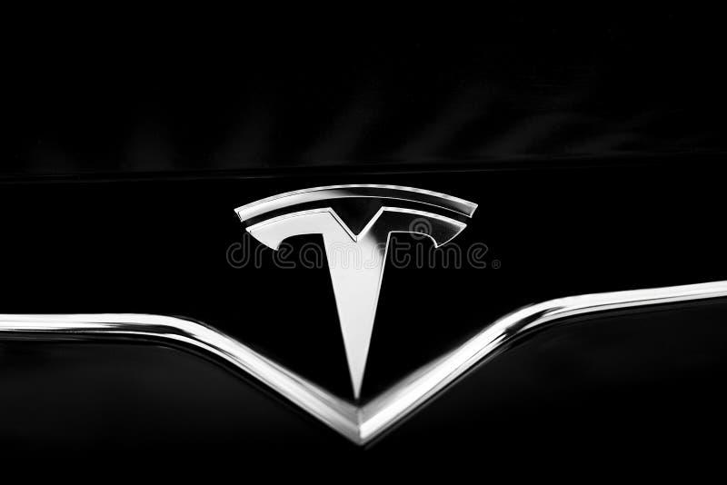 在黑汽车的特斯拉象征 特写镜头银色商标 库存照片