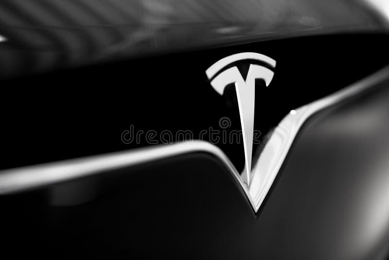 在黑汽车的特斯拉象征 特写镜头银色商标 免版税库存照片