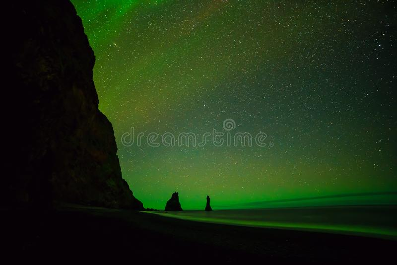 在黑沙子上的北极光在Vik靠岸 库存图片