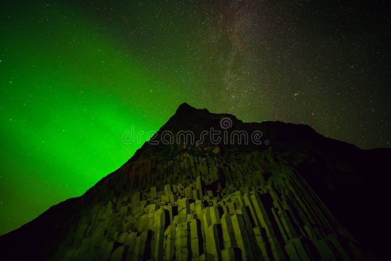 在黑沙子上的北极光在Vik靠岸 库存照片