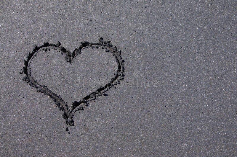 在黑沙滩得出的心形 图库摄影