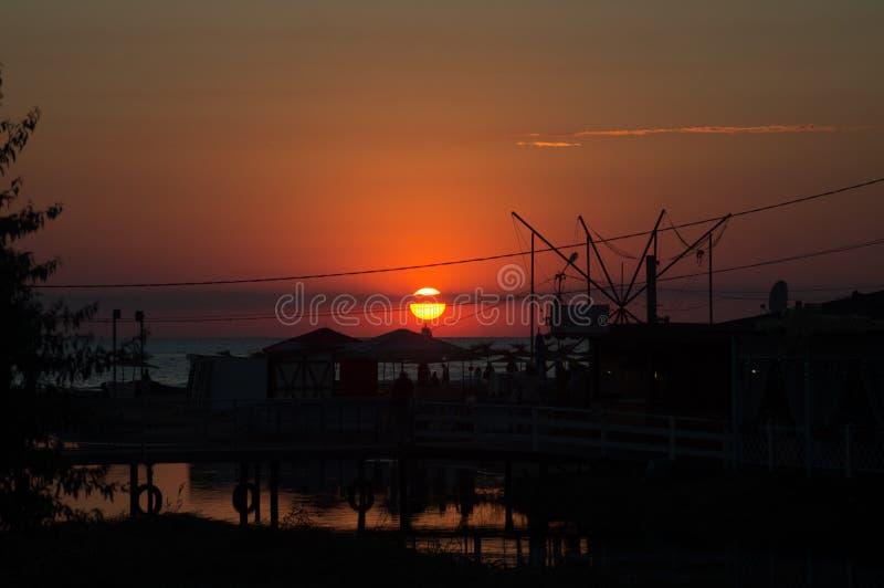 在黑海和橙色天空的美好的燃烧的日落风景在它上与令人敬畏的在镇静波浪的太阳金黄反射作为a 免版税图库摄影