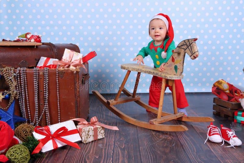 在黑煤炭的纸币谎言 一个小男孩打扮,矮子在圣诞装饰站立 免版税库存照片