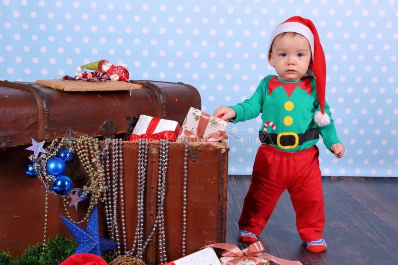 在黑煤炭的纸币谎言 一个小男孩打扮,矮子在圣诞装饰站立 免版税库存图片