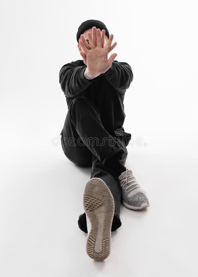 在黑牛仔裤、运动衫、帽子和灰色运动鞋打扮的自由式舞蹈家在演播室跳舞在地板上的开会 免版税库存图片